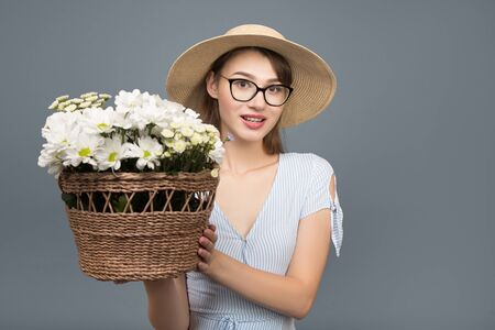 happy young woman smiling. Hold in your hands white flowers in a basket. Enjoy the gift