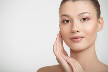 woman with clean skin touches her cheeks with her hand. facial skin concept ongray background