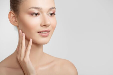 Portrait of a young woman. Bare shoulders. Hand touches face Stock Photo