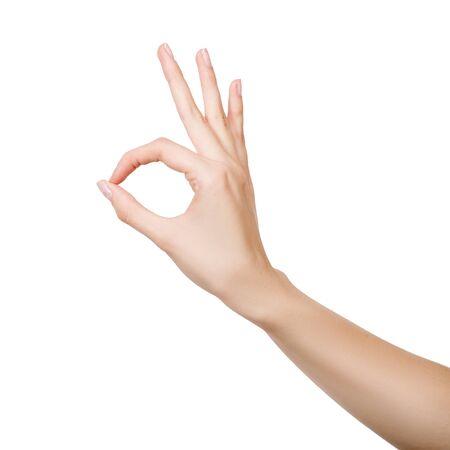 Mano de mujer haciendo signo Ok aislado sobre fondo blanco. Foto de archivo