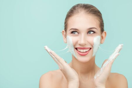 Happy woman is applying a moisturizing mask to her face. blue background