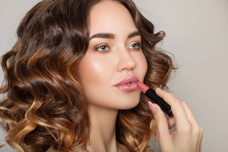 brunette woman with perfect make-up paints her lips. curly beautiful hair. Voluminous hairstyle