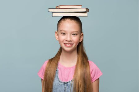 Portrait of a young schoolgirl with books. Copycpase