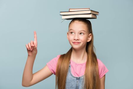 Portrait of a young schoolgirl with books. Holding thumbs up. Copycpase Фото со стока
