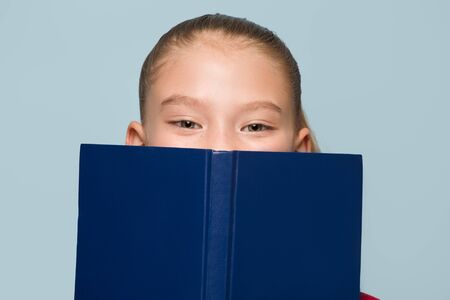 Schoolgirl covers her face with a book. Eyes portrait