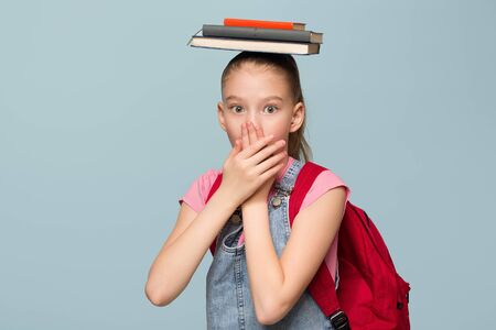 Portrait of a young schoolgirl with books. Cover your mouth with your hands. Copycpase