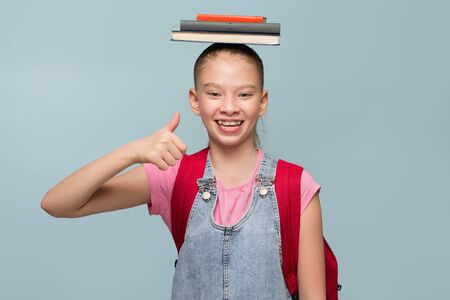 Portrait of a young schoolgirl with books. Thumb up. Copycpase