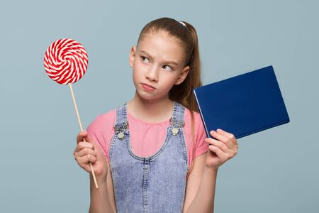 Portrait of a young schoolgirl. The choice between a book and a candy. Thumbs up. Copycpase Фото со стока