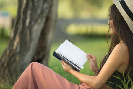 Smiling happy young woman is reading a book. Girl rest in the park. Copycpase 스톡 콘텐츠