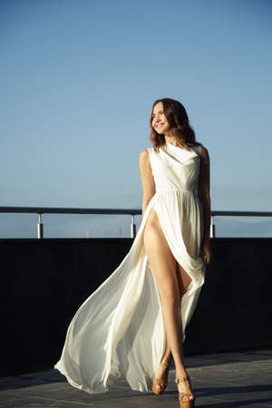 Beautiful fashion woman in a long white dress. Urban environment Banque d'images