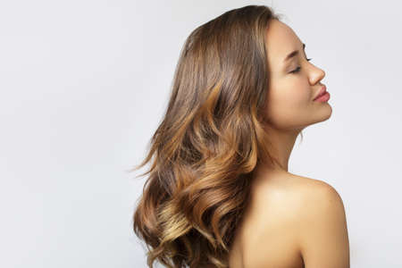 Portrait of a woman showing her. Thick shiny wavy ombre hair. Back view