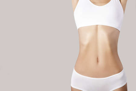 flat belly and slender figure of a woman. Gray background. copycpase 版權商用圖片