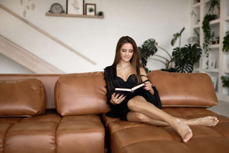 Smiling woman in fashion home clothes reading a book while sitting on the sofa 版權商用圖片