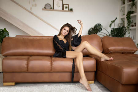 attractive woman in silk robe and black lingerie sitting on the sofa at home