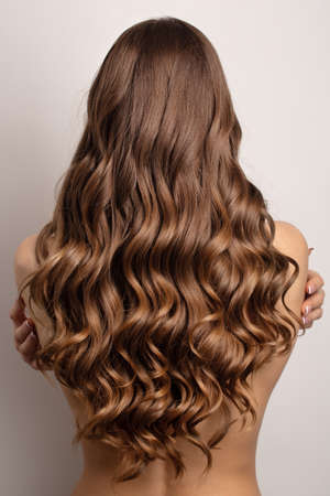 wavy brown hair back view. Gray background