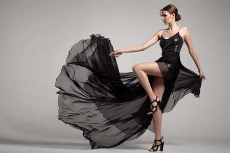 Woman fashion black long dress. On a gray background Reklamní fotografie