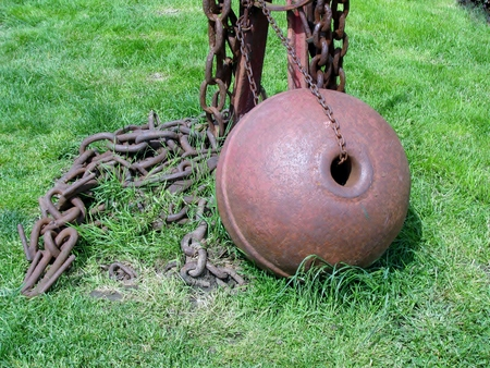 Iron rusty ball and chain on a green grass photo