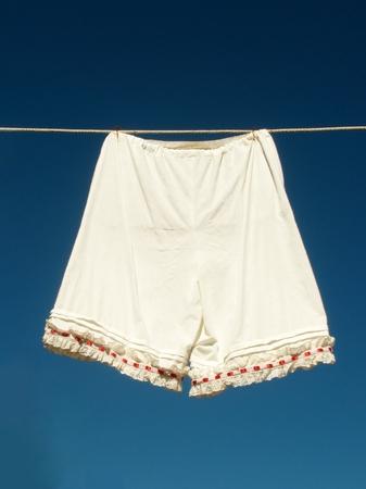 De vvintage vrouwen ondergoed opknoping op een waslijn tegen blauwe hemel Stockfoto