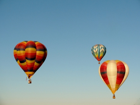 Three hot air balloons in blue sky