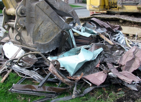 house demolition: Close-up of excavator bucket loading metal parts from house demolition site