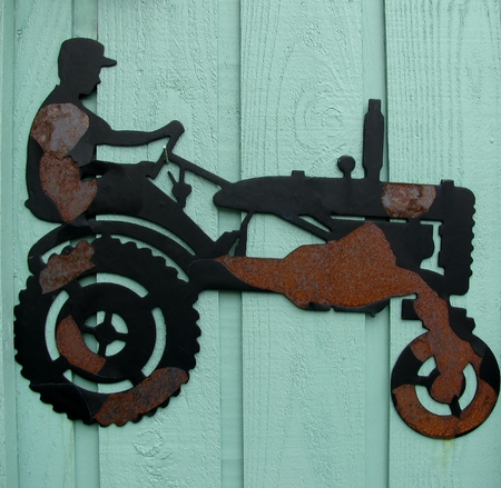 american field service: Tractor wrought iron detail on blue wall