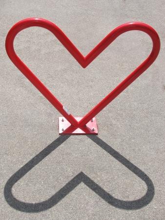 Heart-shaped bike rack and its shadow Stock Photo