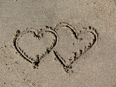 entangled: Two overlapping hearts drawn out on a sandy beach