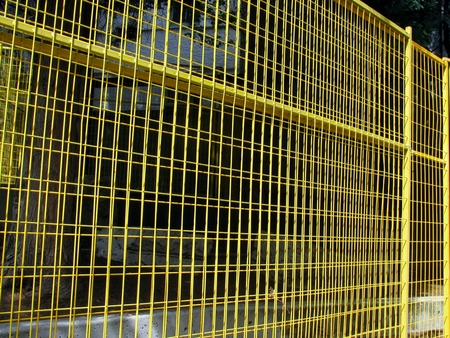 wire fence: Yellow metal wire fence Stock Photo