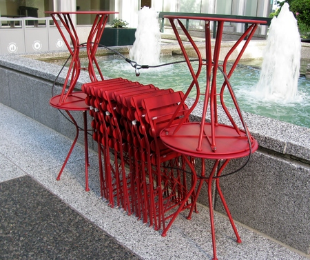 round chairs: Red tables and chairs neatly stacked