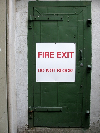 wayout: Fire exit do not block! sign on a green door Stock Photo