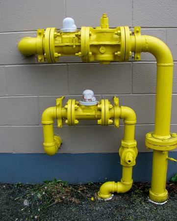 Concrete wall , yellow pipes, plumbing industry.