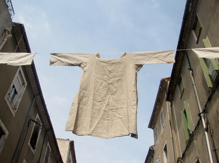 undergarment: Undergarment shirt  hanging on a clothesline between the buildings Stock Photo