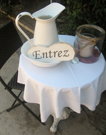 come in: Vintage interior with a table, pitcher, candle and Come in sign