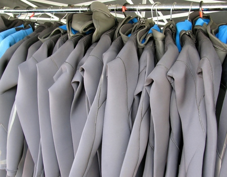 Line of multiple hanging wetsuits. Stock fotó