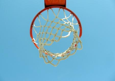 Closeup of an outdoors basketball basket over the blue sky