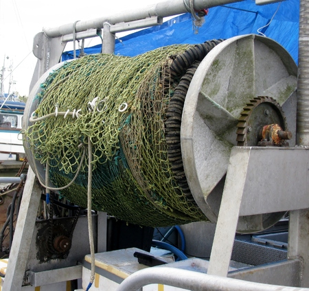 Purse seine fishing net on reel at the back of a fishing boat.