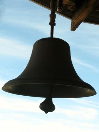 Black bronze bell against blue sky
