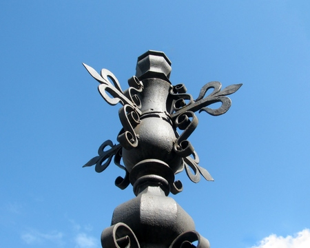 Detail of metallic street pole with decorative fleur-de-lis Stock Photo