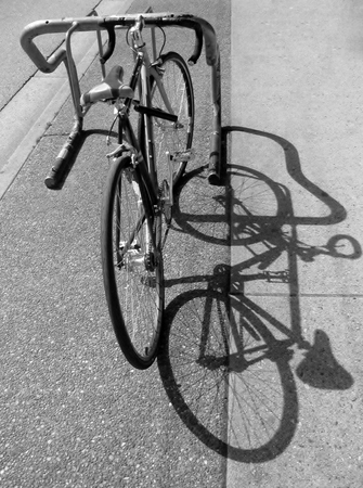 road cycling: Parked bicycle and its shadow Stock Photo