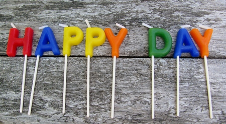Happy day candles on a wooden background