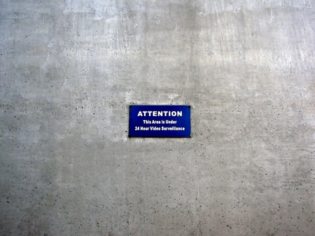 Attention this area is 24 hour under surveillance sign on grey concrete wall