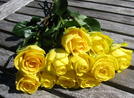 Bouquet of yellow roses left on wooden table Stock Photo