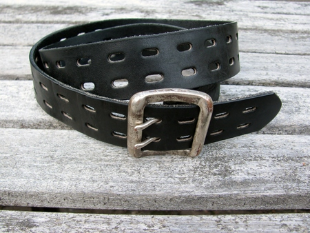 Rough leather belt on wooden background