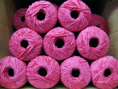 Set of bright pink rayon chenille yarn balls in a carton box Stock Photo