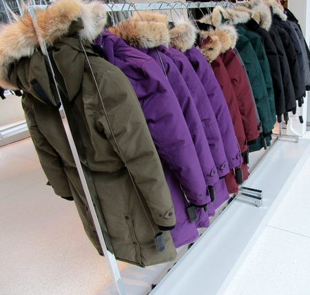 Colorful coats, jacket with fur on hood hanging on clothes rack for sale.