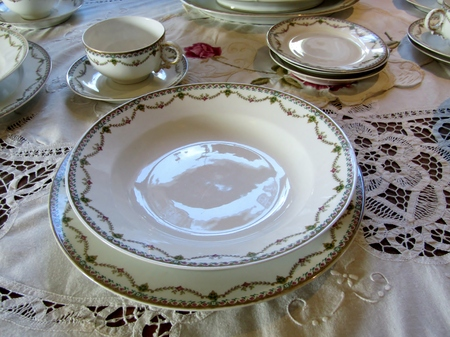 Vintage china dinnerware set and lace tablecloth Stock Photo