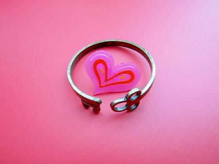 Key cuff bracelet bent around pink heart Stock fotó