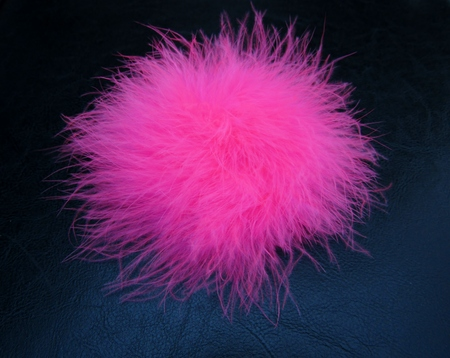 Pink fluffy feather ball on black background Foto de archivo