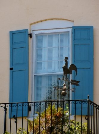 Sash window with blue shutters and iron rooster weather vane at balcony Imagens