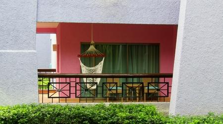 White woven hammock with wooden spreader bar on pink balcony, Riviera Maya, Yucatan Peninsula, Mexico